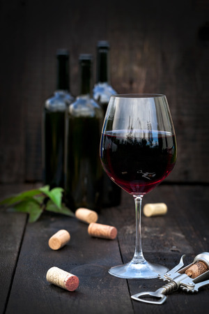 Glass of red wine with corks on old wooden table photo