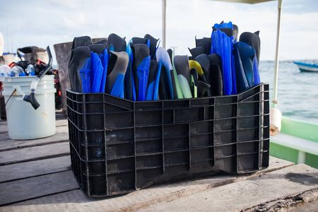 diving equipment: Diving equipment, set of blue flippers in plastic box on wooden pier with sea background