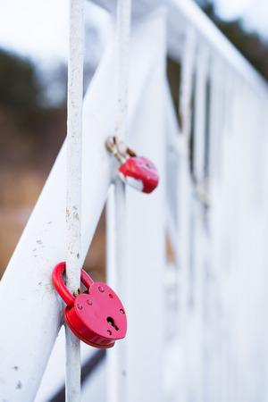 Love romantic padlocks locked on fence of the white bridge photo