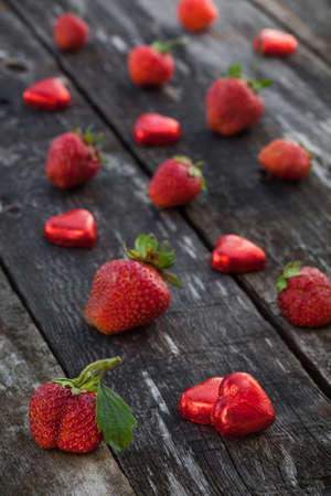 Fresh red strawberries and chocolate heart candy on old wooden table photo