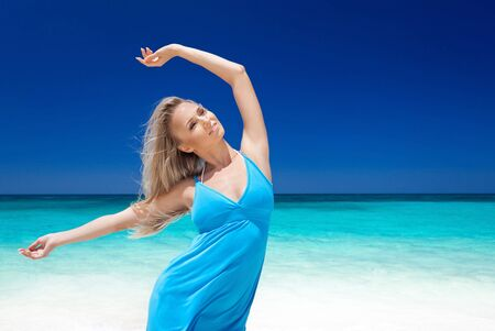 Happy blond girl on beach, feeling freedom and enjoying life. Vacation concept. Free copyspace. photo