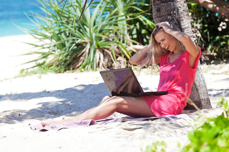 Blond girl with a laptop on tropical beach sitting under coconut palm, freelance concept. photo