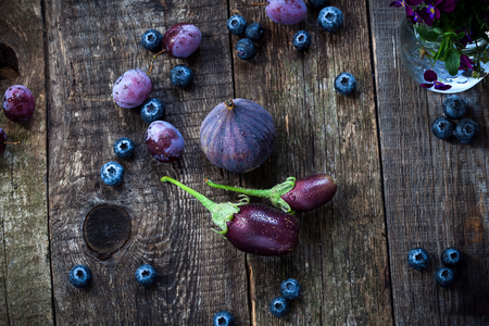 Purple color in vegetables - blueberry, plums, aubergine and figs on old wooden background photo