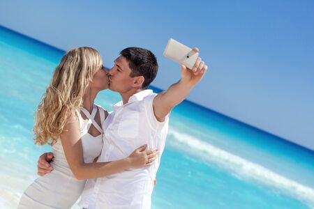 Happy couple taking a photo on a beach with turquoise sea background. Travel vacation concept photo