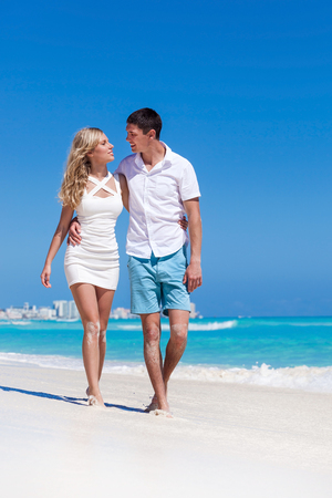 Romantic couple walking on perfect beach with turquoise sea, enjoying life and each other at honeymoon vacation. photo