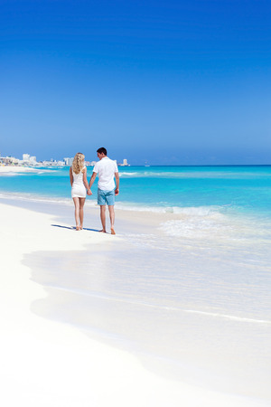 Romantic couple walking on perfect beach with turquoise sea, enjoying life and each other at honeymoon vacation. Back view photo