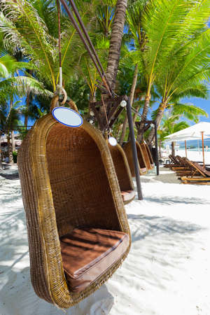 philippines: Empty hanging wicker chair on tropical beach, Philippines, Boracay Stock Photo