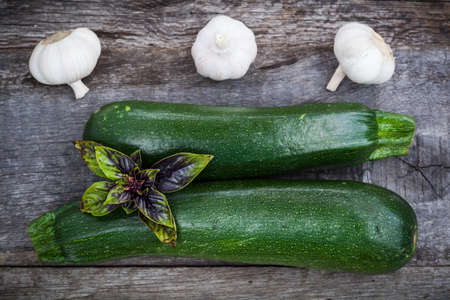 cucurbit: Fresh green zuchinni with basil leaves and garlic on wooden board, top view