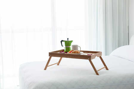 percolator: Breakfast wooden tray with coffee percolator and croissant on bed