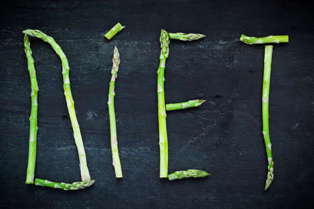 bundle of letters: Word Diet made of asparagus vegetables on black wooden board, top view. Healthy food concept