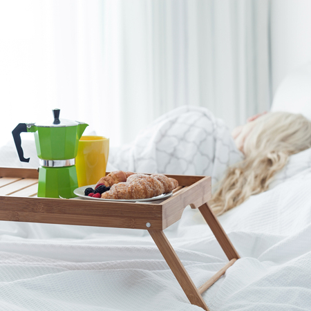 percolator: Breakfast wooden tray with coffee percolator and croissant on bed, sleeping woman background. Romantic morning surprise.