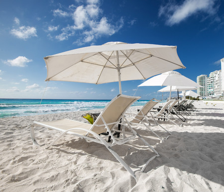 Caribbean beach with sun umbrellas and beds, Cancun, Mexico photo