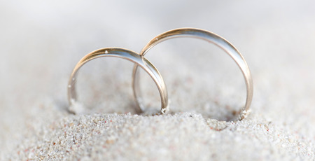 silver wedding anniversary: Wedding rings in sand on tropical beach Stock Photo
