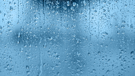 blue tone: Raindrops on the window, abstract background. Blue tone