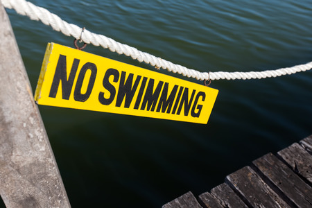 no swimming: No swimming sign on wooden tablet near lagoon