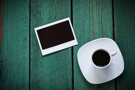 memoir: Empty photo card and a cup of coffee on old green wooden board, memory concept