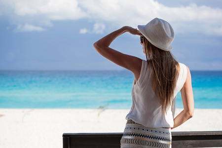 balcony: Woman in summer hat on balcony looking to the turquoise sea and white perfect sandy beach, enjoying life and summer vacation, rear view Stock Photo