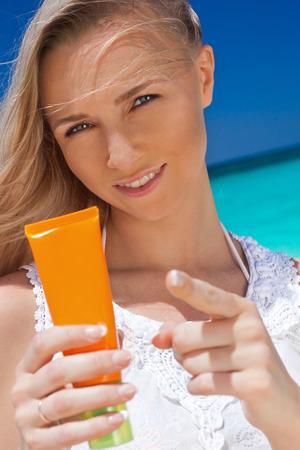suncare: Portrait of woman holding sunscreen cream on beach, beauty concept