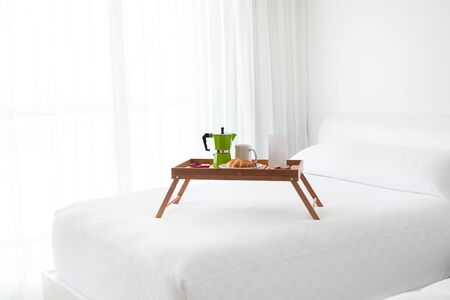 Breakfast wooden tray with coffee percolator, white blank card and croissant on bed. Light from window inside the room photo