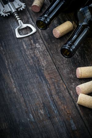 corcho: Botella de vino, corchos y sacacorchos sobre fondo de madera