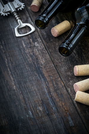 cork wood: Bottle of wine,  corks and corkscrew on wooden background