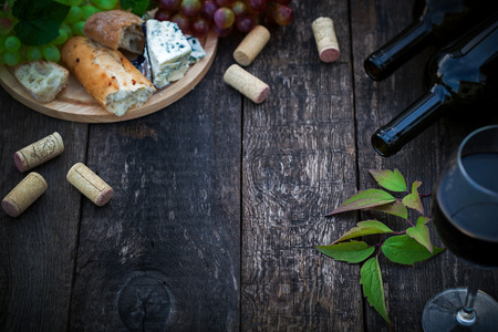 Wine bottles with grape leaves on wooden background with copy space