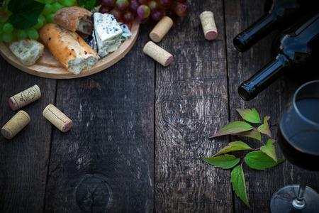Wijnflessen met druivenbladeren op houten achtergrond met kopie ruimte