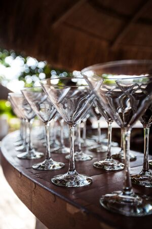 palapa: Empty Martini glasses setting in row, outside on wooden bar counter at tropical grass palapa,  ready for celebration party, selective focus