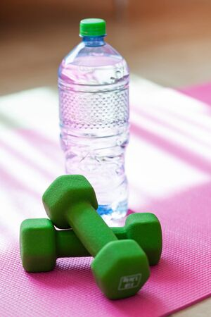 yoga mat: Two dumbbells with mineral water on yoga mat, sporty lifestyle concept