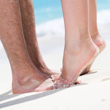 beach kiss: Womans barefoot legs standing up tiptoe closeup to male foot and kissing on sandy beach with turquoise sea background, no face. Happy romantic holidays concept.