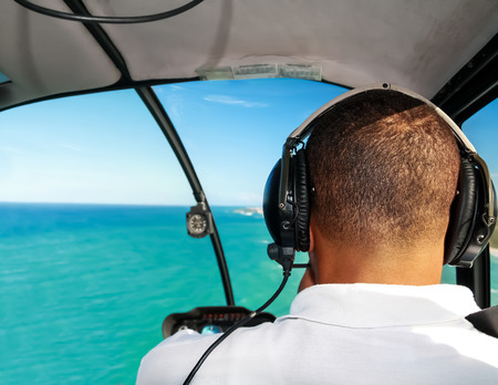 helicopter pilot: Helicopter pilot in flight with caribbean sea aerial view