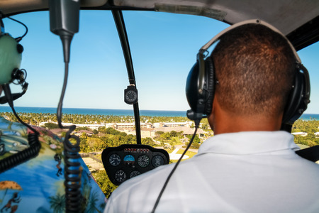 Helicopter pilot in flight with tropical nature aerial view Stock Photo