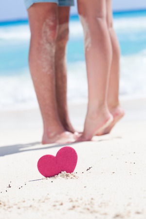 footsie: Barefoot female legs standing up tiptoe on mans foots on beach with turquoise sea background, decorated pink heart object.  Romantic honeymoon vacation concept