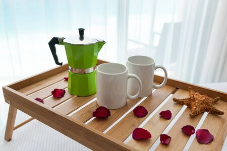 percolator: Breakfast wooden tray with coffee percolator and two cups on bed, decorated roses petals Stock Photo
