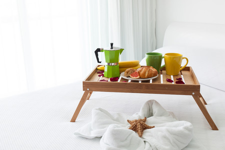 percolator: Breakfast wooden tray with coffee percolator and croissant on bed, decorated starfish on white towel