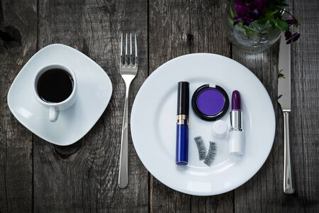 fake eyelashes: A cup of morning coffee,  lipstick, eyeshadow and fake eyelashes on plate on old wooden board, beauty concept of purple colors