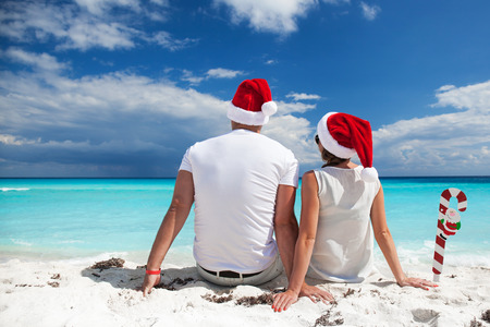 Happy couple celebrating Christmas on beach