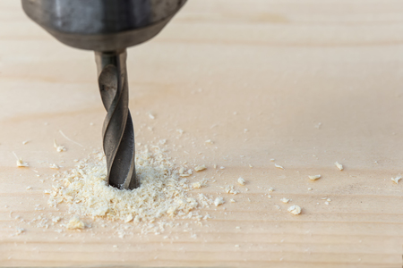 swarf: Drilling wooden plank with hand drill, closeup