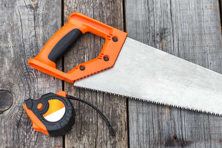 handsaw: Handsaw and  measuring tape on a wooden board, closeup