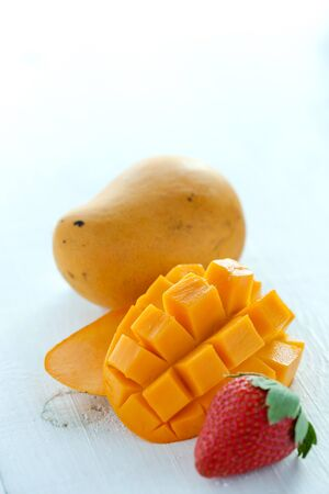cutted: Fresh cutted cube mango and strawberry on white wooden background