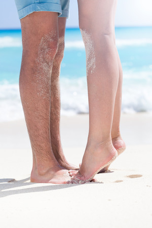 footsie: Womans barefoot legs standing up tiptoe closeup to male foot and kissing on sandy beach with turquoise sea background, no face. Happy romantic holidays concept.