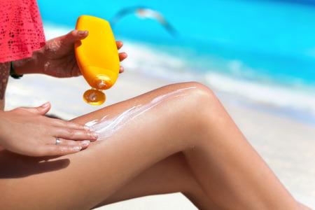 proteccion: Tan delgada mujer de aplicar protector solar en sus piernas, sentado en la playa de arena con el mar de fondo. Concepto de protección SPF bloqueador solar. Vacaciones Viajes