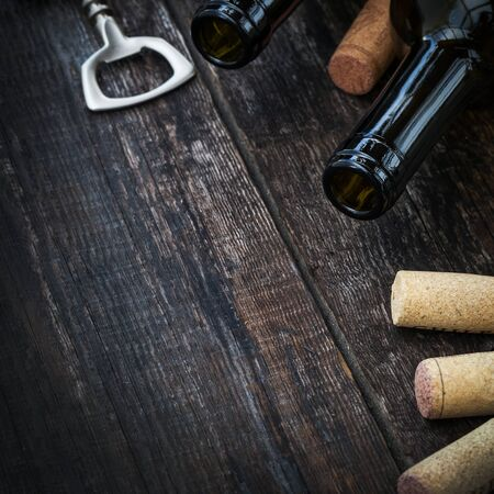 white wine bottle: Bottle of wine,  corks and corkscrew on wooden background