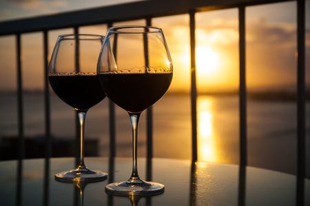 bebiendo vino: Dos vasos de vino tinto en frente de la puesta de sol. Vista del balc�n con el fondo del mar Caribe