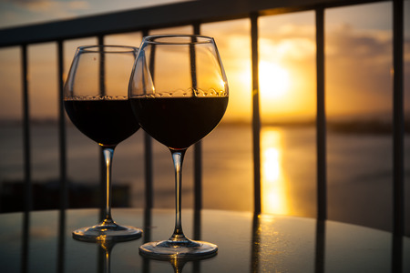 Two red wine glasses in front of the setting sun. Balcony view with Caribbean sea background