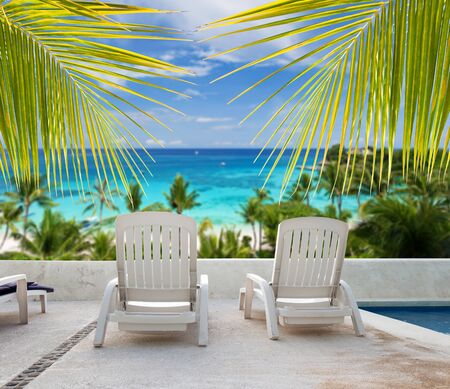 seaview: Tropical vacation. Seaview from luxury resort balcony through palm tree leafs Stock Photo