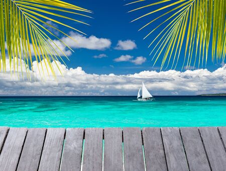 summer fruits: Wooden pier with view on sailboat in the ocean