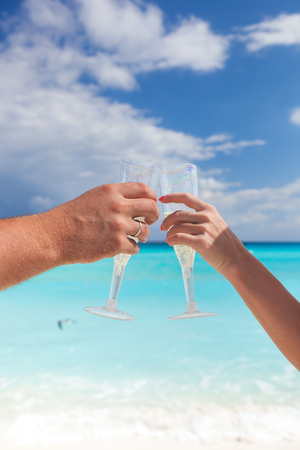Clanging glasses with champagne at sandy beach and sea background, shallow depth Stock Photo