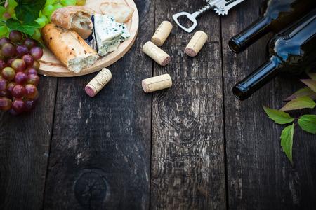 corcho: Botellas de vino con uva hojas sobre fondo de madera con espacio de copia, enfoque selectivo Foto de archivo