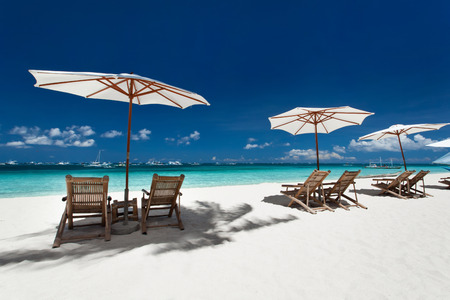 sun umbrellas: Sun umbrellas and wooden beds on tropical beach. Caribbean vacation